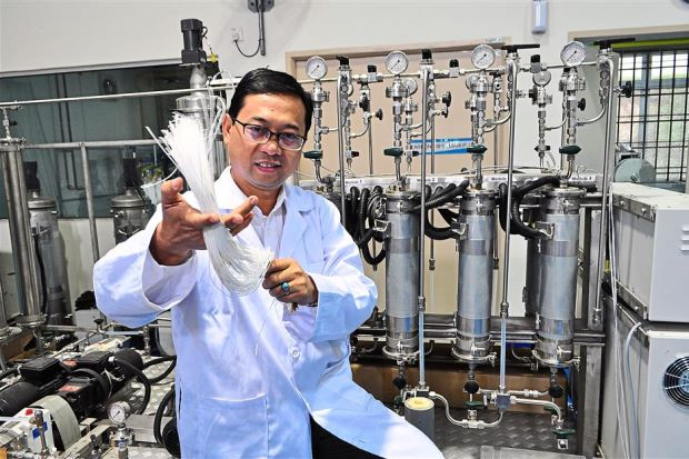 Prof. Dr. Ahmad Fauzi with a test purification ensemble scaled down 10 times its actual size.
